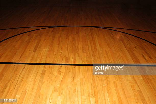 Bare basketball wood floor with black court lines