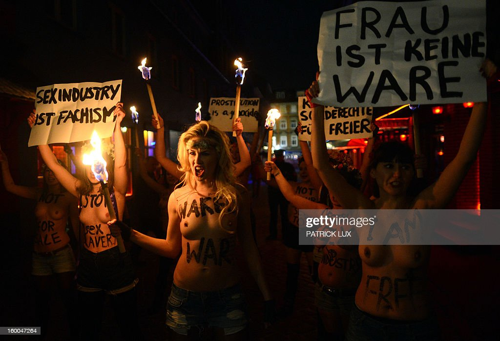 Bare chested activists of Femen, a Ukranian feminist movement, hold torches and a banner (R) that reads 'A woman is not a commodity' to protest against prostitution in the red light district Herbertstrasse in Hamburg, northern Germany on January 25, 2013. The activists .