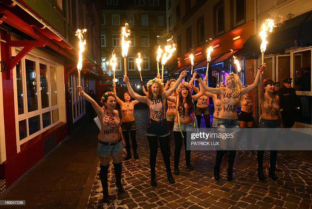 Bare chested activists of Femen, a Ukranian feminist movement, hold torches as they protest against prostitution in the red light district Herbertstrasse in Hamburg, northern Germany on January 25, 2013. The activists .