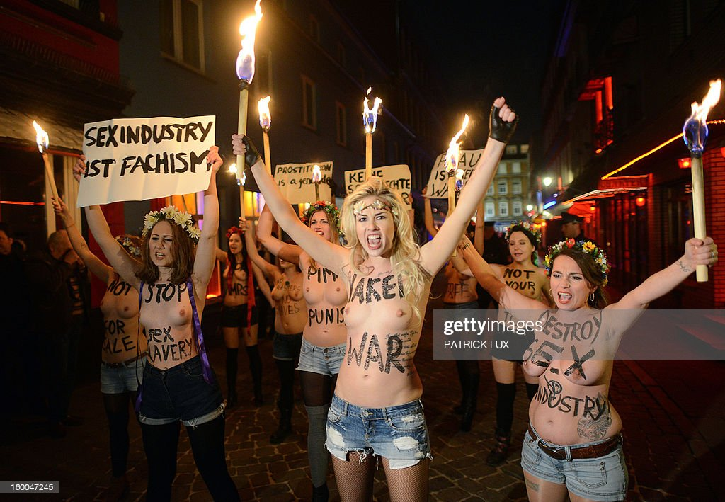 Bare chested activists of Femen, a Ukranian feminist movement, hold torches as they protest against prostitution in the red light district Herbertstrasse in Hamburg, northern Germany on January 25, 2013. The activists . AFP PHOTO / PATRICK LUX