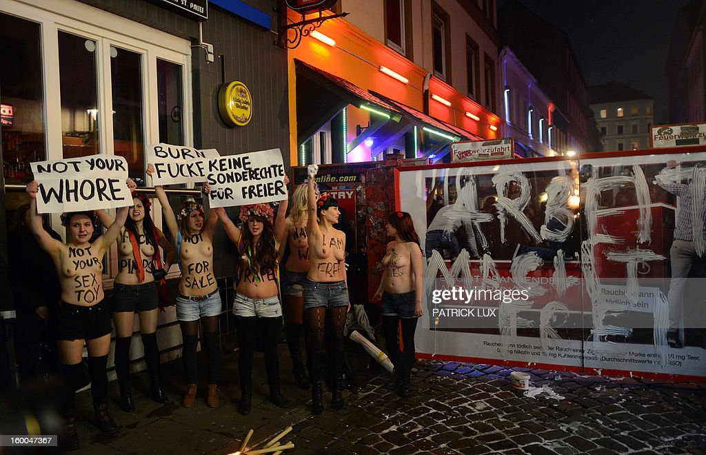 Bare chested activists of Femen, a Ukranian feminist movement, protest against prostitution next to a slogan 'Work makes you free' painted on the entrance of Herbertstrasse, the red light district in Hamburg, northern Germany on January 25, 2013.