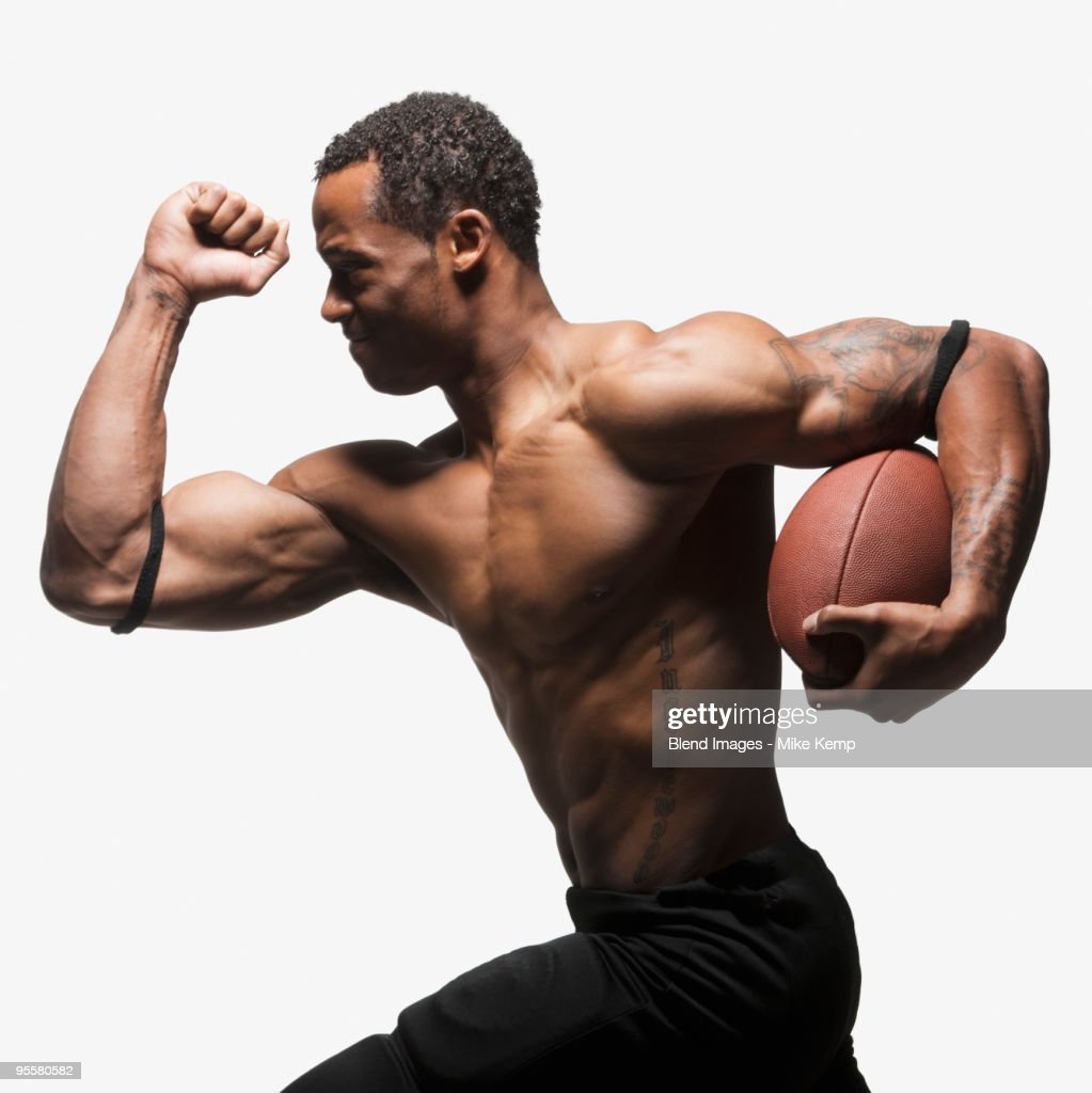 Bare chested football player running with football : Stock Photo
