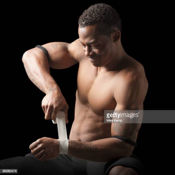 Bare chested football player taping wrist