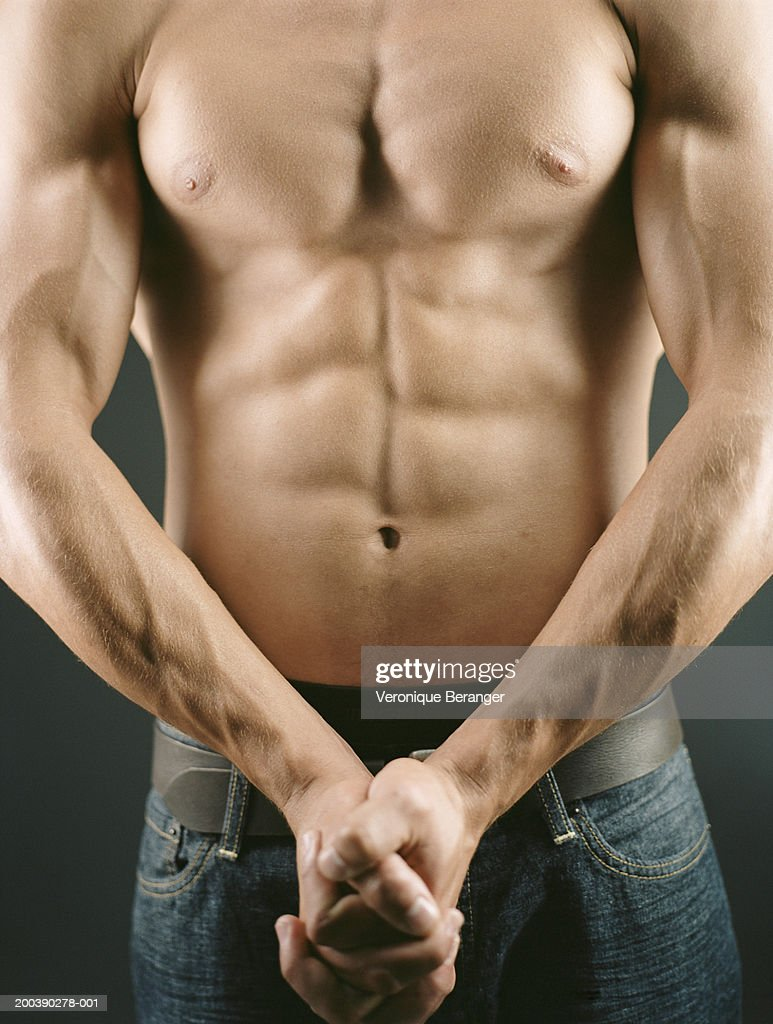 Bare chested man flexing arm and chest muscles, mid section : Stock Photo
