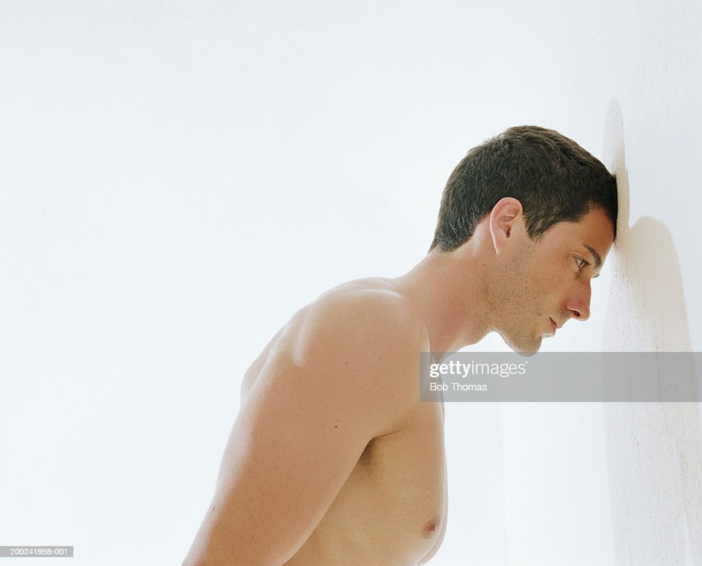Bare chested man resting forehead against wall, side view : Stock Photo