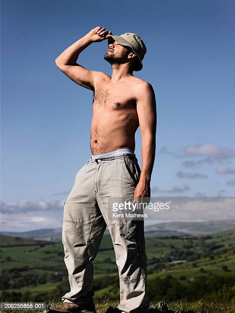 Bare chested man standing outdoors, holding hat