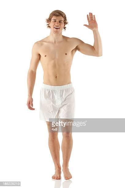 Bare chested Mann zu Fuß und winkt hand