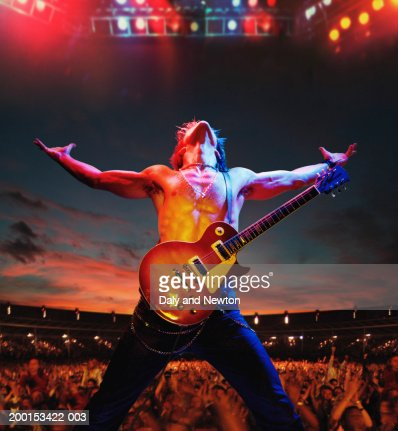 Bare chested man with guitar on stage by crowd, arms outstretched