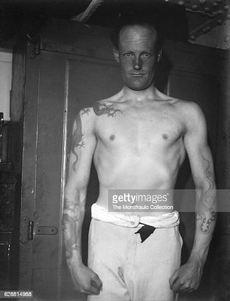 Bare chested Royal Navy Sailor Bannerman Flashlight with his arms covered with elaborate Chinese dragon and snake tattoos standing to attention on...