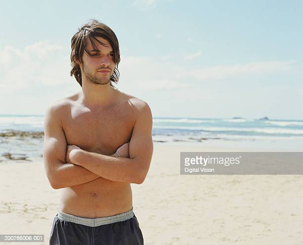 Bare chested young man on beach, arms folded, looking away