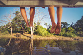 Two pairs of bare feet hanging off the roof of a boat on a tourboat on the Chobe River during a safari with the river and wilderness of the Chobe National Park in view and an African elephant walking