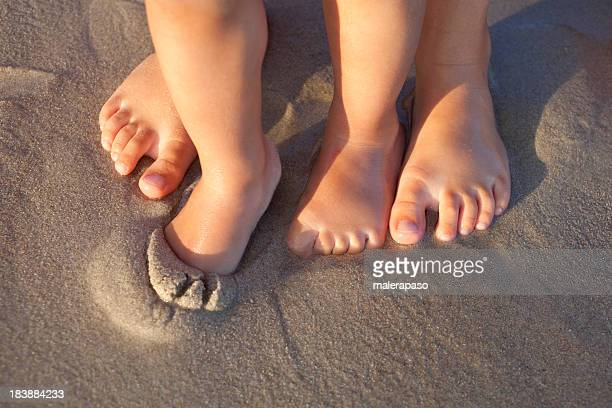 Bare feet in wet sand on beach