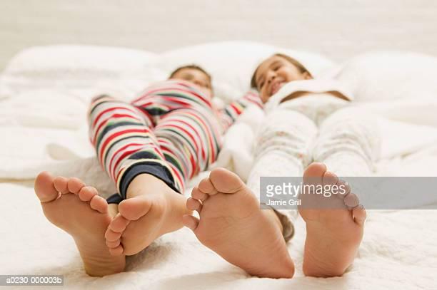 Bare Feet of Children on Bed