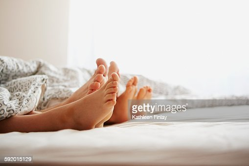 Bare feet of parents and son lying in bed