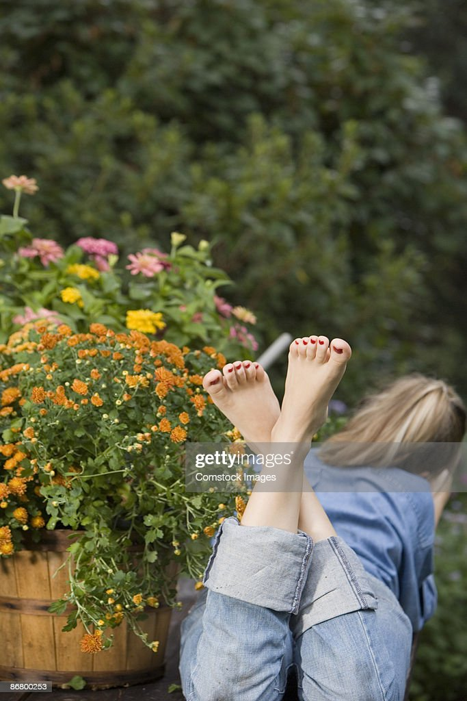 Bare feet of woman lying on table in garden : Stock Photo