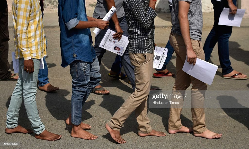 Bare foot students stands in queue at the gate of examination entree after they were thoroughly scanned to take the All India Pre-Medical/Pre-Dental Entrance Test (AIPMT) at the examination centre at RK Puram on May 1, 2016 in New Delhi, India. The All Indian Pre-Medical Test (AIPMT) 2016, being treated as the first phase of the National Eligibility Entrance Test (NEET), was held on Sunday. The competitive examination held for entrance to MBBS and BDS courses across the country was held amidst tight security this year. Students had a proper dress code to adhere to as they were not allowed to enter the examination hall in shoes or carry any kind of stationary with them. Mobile phones were also not allowed