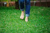 bare foot preson in jeans walking in green grass