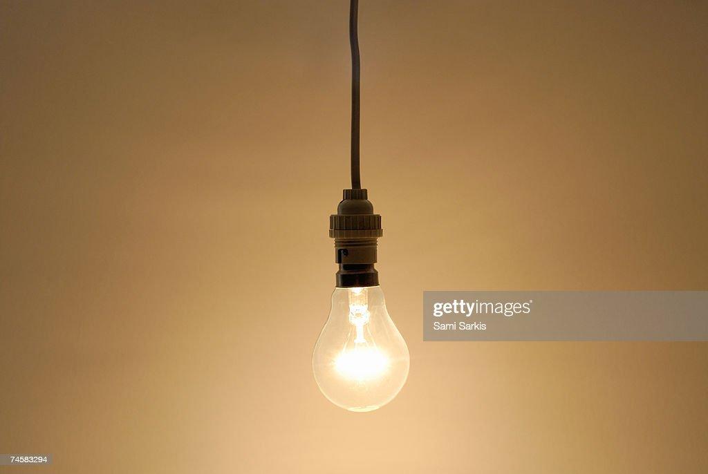 Bare hanging light bulb in studio : Stock Photo