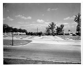 Bare land with sidewalk and quiet street next to construction lots of trees and street lights in background Baltimore Maryland 1930