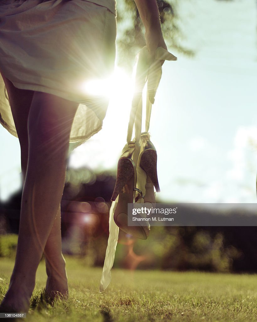Bare legs woman walking in grass : Stock Photo
