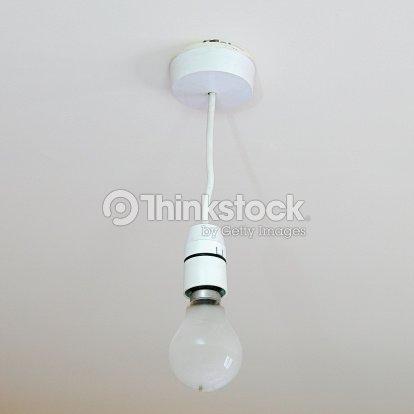 Bare light bulb hanging from ceiling foto de stock thinkstock bare light bulb hanging from ceiling foto de stock aloadofball Choice Image