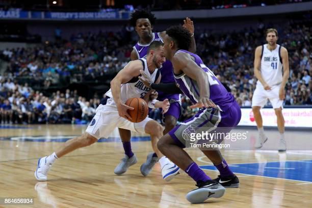 J Barea of the Dallas Mavericks drives to the basket against De'Aaron Fox of the Sacramento Kings and Buddy Hield of the Sacramento Kings at American...
