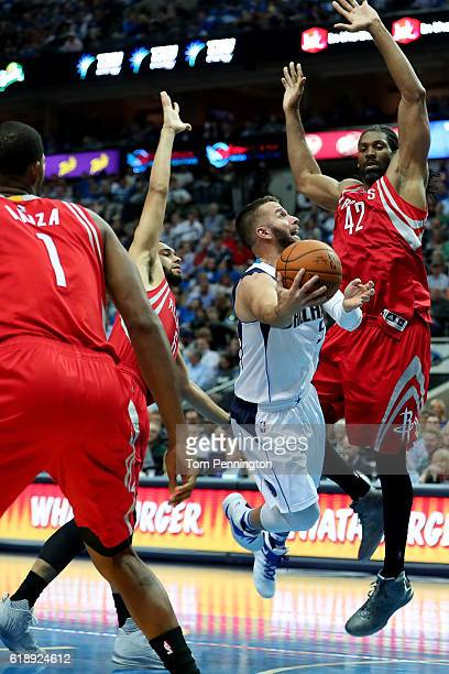 J Barea of the Dallas Mavericks drives to the basket against Trevor Ariza of the Houston Rockets Tyler Ennis of the Houston Rockets and Nene Hilario...