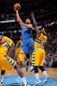 J Barea of the Minnesota Timberwolves lays up a shot against Ty Lawson of the Denver Nuggets at Pepsi Center on November 15 2013 in Denver Colorado...