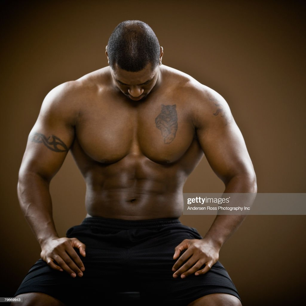 Bare-chested African man with head down : Stock Photo