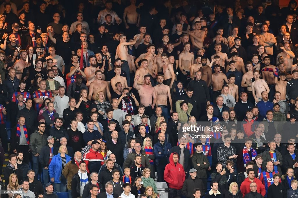 Bare-chested Crystal palace fans cheer on their team during the English League Cup third round football match between Crystal Palace and Huddersfield Town at Selhurst Park in south London on September 19, 2017. / AFP PHOTO / Glyn KIRK / RESTRICTED TO EDITORIAL USE. No use with unauthorized audio, video, data, fixture lists, club/league logos or 'live' services. Online in-match use limited to 75 images, no video emulation. No use in betting, games or single club/league/player publications. /
