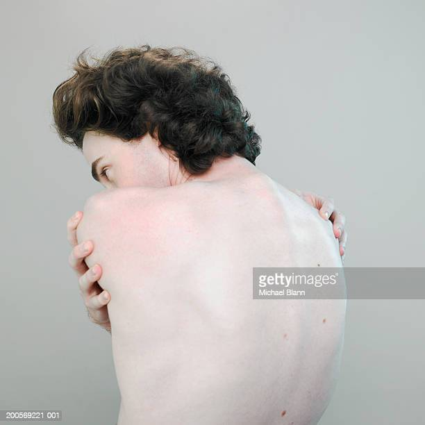 Barechested man embracing self, close-up
