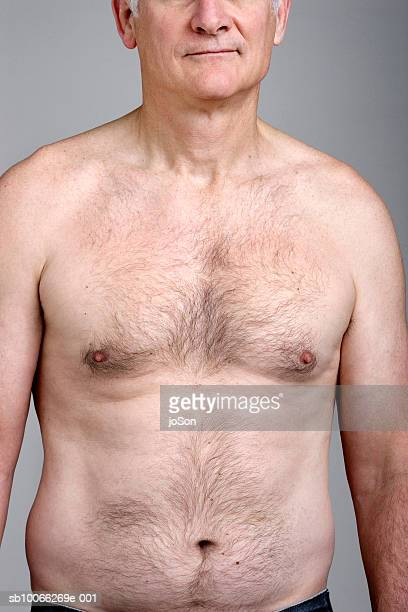 Barechested man standing against grey background, close-up, mid section
