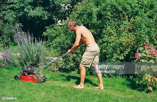 Barechested Mature Man Mowing Lawn
