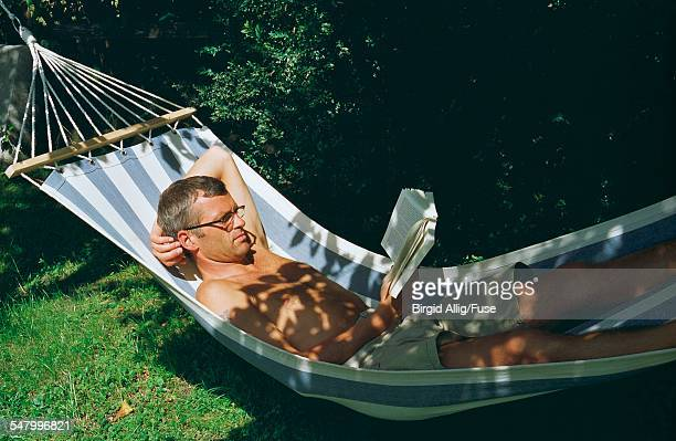 Barechested Mature Man Reading Book in Hammock