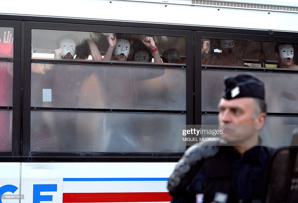 Bare-chested men wearing white masks and belonging to an anti-gay group (Hommen), shout slogans as they are detained in a police bus during a demonstration against a bill legalizing same sex marriages on May 17, 2013 in Paris. After months of acrimonious debate and hundreds of protests that have occasionally spilled over into violence, France's National Assembly approved on April 23, 2013 a bill making the country the 14th to legalise same-sex marriage.
