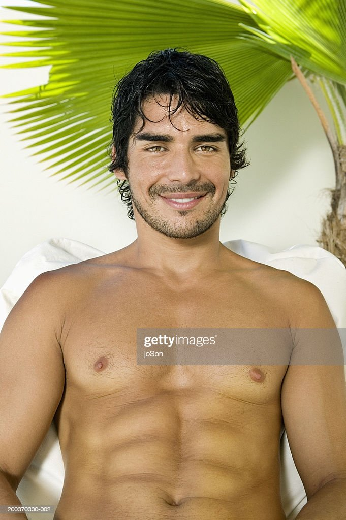 Bare-chested young man smiling, palm tree in background, portrait : Stock Photo