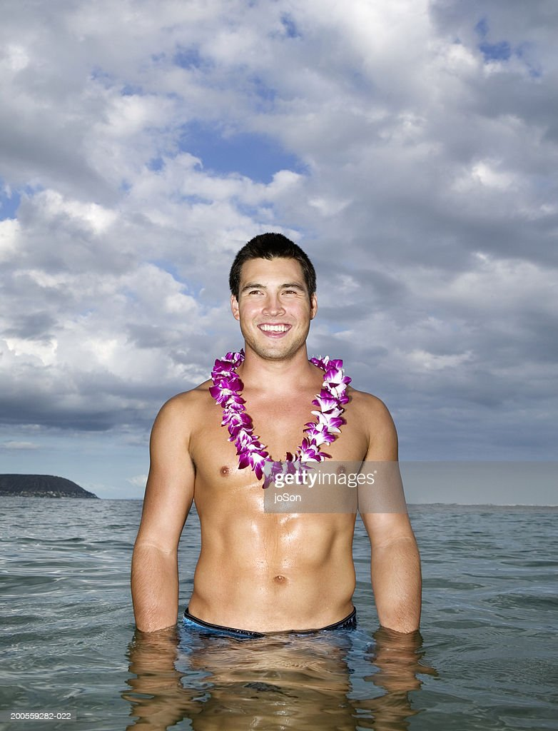 Barechested young man standing in sea, smiling : Stock Photo