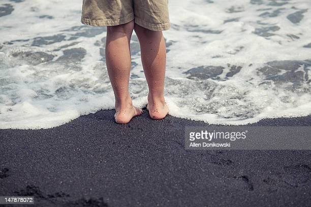 Barefeet in cold water at black sand beach