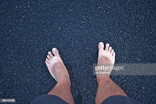 Barefeet with sandal tan on black sand beach