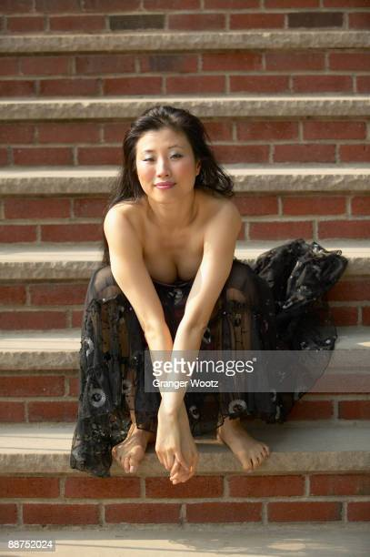 Barefoot Asian woman in evening gown on steps