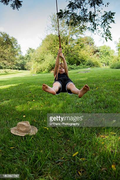 barefoot boy on rope swing with hat