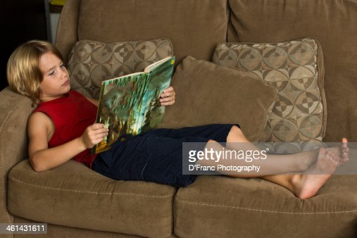 Barefoot Boy Reading Book On Sofa Stock Photo | Getty Images