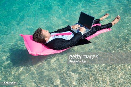 素足に浮かぶノートパソコンでの作業の実業家の熱帯の海