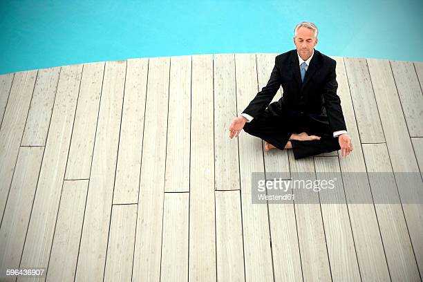 Barefoot businessman wearing black suit meditating in front of swimming pool