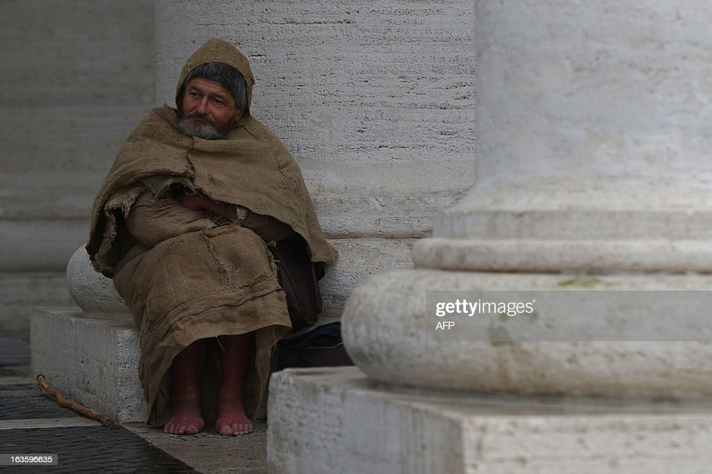 A barefoot faithful stands under the colonnade on St Peter's square on March 13, 2013 at the Vatican. Cardinals prepared for a second day of conclave behind the Vatican's walls to elect a pope today, with all eyes on a chimney that will signal when there is a new leader for the world's 1.2 billion Catholics. The 115 cardinals held a first inconclusive vote in the Sistine Chapel on Tuesday as they began the process of finding a successor to Benedict XVI, who brought a troubled eight-year papacy to an abrupt end by resigning last month. AFP PHOTO / GABRIEL BOUYS