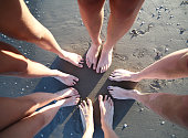 Barefoot feet of a family of five person with long legs on the sandy beach forming a circle on the shore