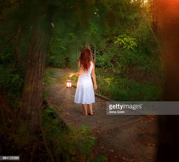 Barefoot girl in forest with lantern, rear view