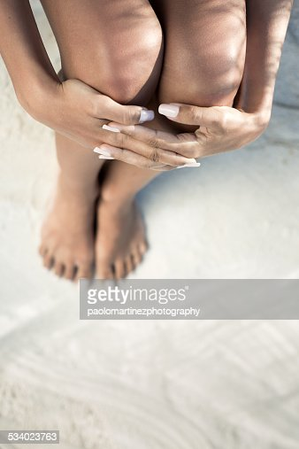 Barefoot girl sitting with hands on knees