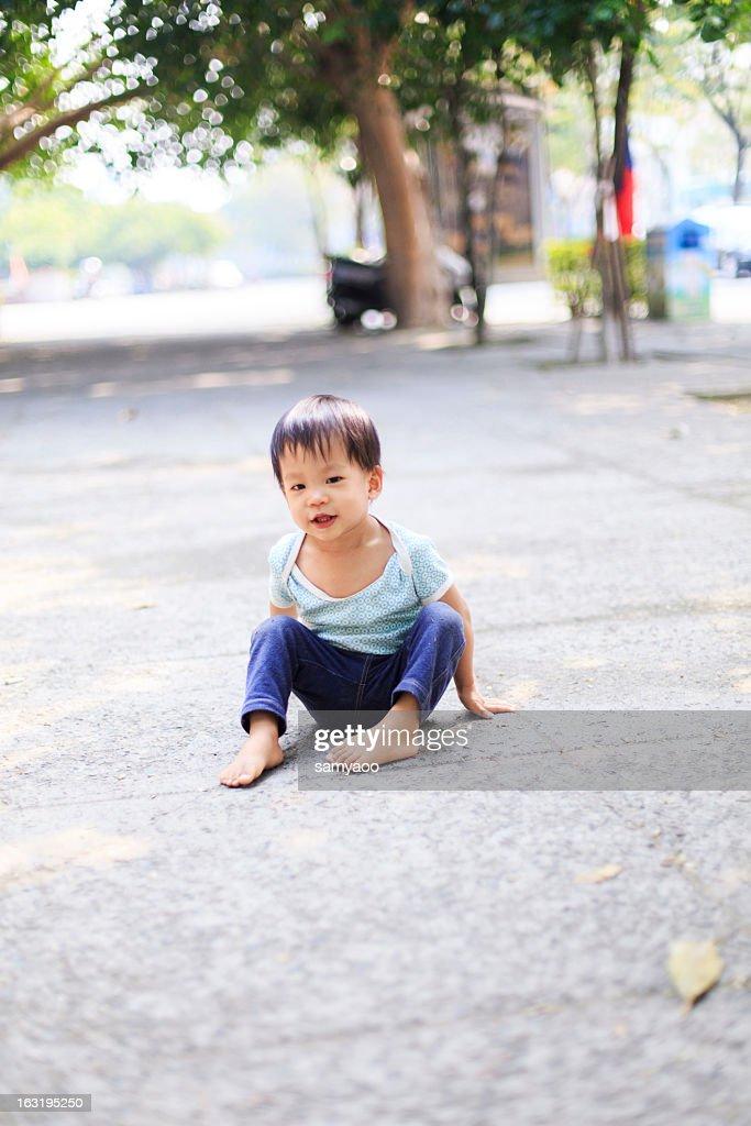 Barefoot little boy sitting on ground : Stock Photo