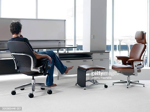 Barefoot man sitting at desk, rear view